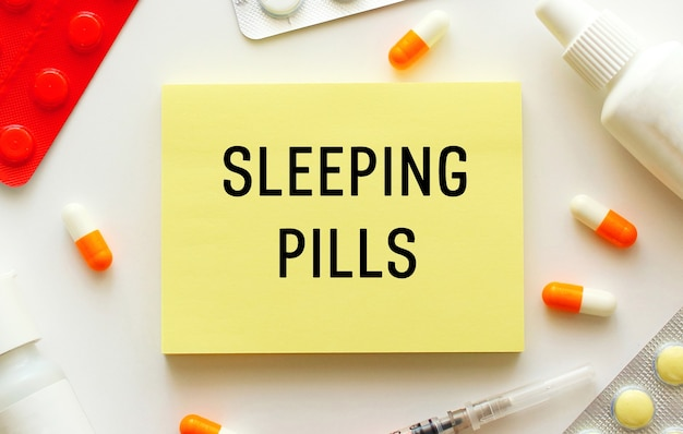 白い表面にテキストの睡眠薬が書かれたメモ帳。近くには様々な薬があります。