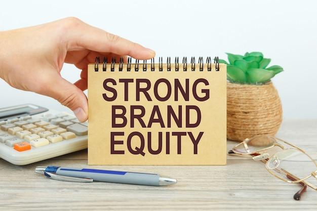 계산기 및 사무 용품 근처 흰색 배경에 텍스트 강력한 브랜드 주식 메모장.