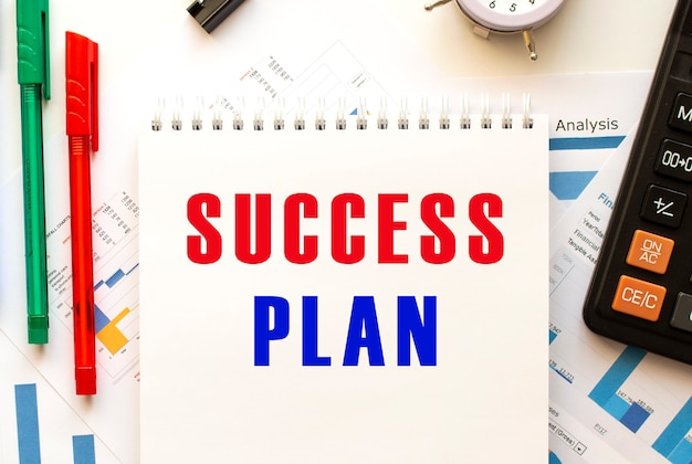 Notepad with the text success plan on a color financial chart