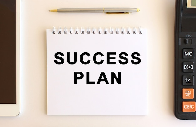 Notepad with text success plan on a white background.