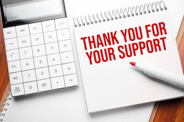 Блокнот с текстом спасибо за вашу поддержку на деревянном фоне с калькулятором и красным маркером
