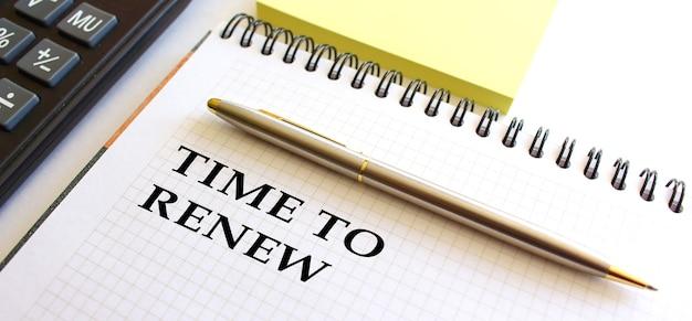 Блокнот с надписью time to renew, рядом калькулятор и желтые заметки.
