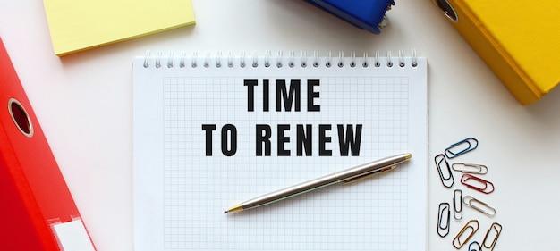 ドキュメントフォルダと事務用品の近くの白い表面に「更新する時間」というテキストが記載されたメモ帳