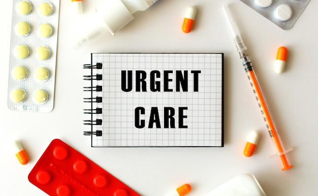 白い背景にテキスト緊急ケアのメモ帳。近くには様々な薬があります。医療の概念。