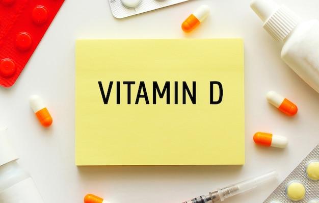 白い背景にテキストビタミンdのメモ帳。近くには様々な薬があります。