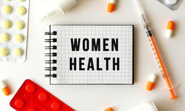 Блокнот с текстом женское здоровье на белом фоне. рядом разные лекарства. медицинская концепция.