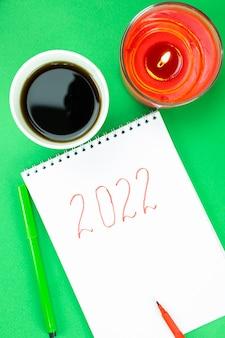 Блокнот с надписью 2022, свеча и кофе на зеленом фоне рождества. новогоднее украшение.