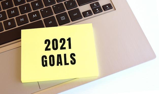 2021 goals 텍스트가있는 메모장이 노트북 키보드에 있습니다.