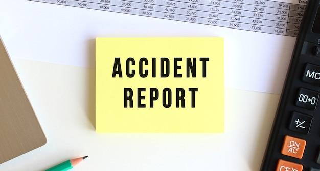 デスクトップ、ラップトップ、電卓、事務用品の近くに「accidentreport」というテキストが書かれたメモ帳。ビジネスコンセプト。