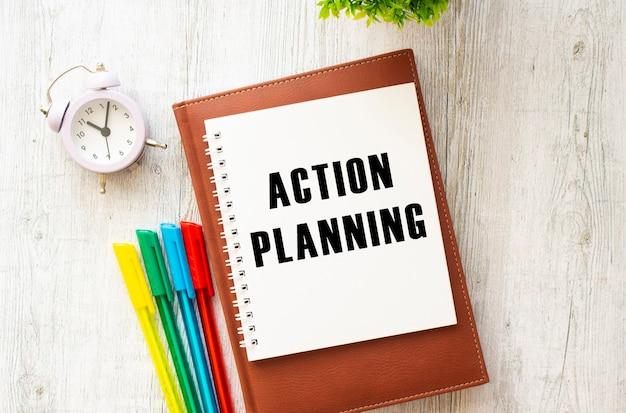 木製のテーブルに「アクションプランニング」というテキストが書かれたメモ帳。茶色の日記とペン。
