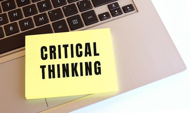 Critical thinking이라는 텍스트가있는 메모장이 노트북 키보드에 있습니다. 최소한의 작업 공간.