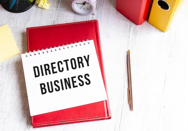 木製のテーブルに「directorybusiness」というテキストが書かれたメモ帳。赤い日記とペン。