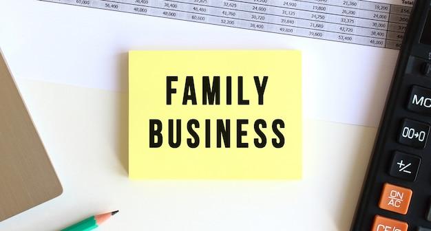 デスクトップ、ラップトップ、電卓、事務用品の近くに「familybusiness」というテキストが書かれたメモ帳