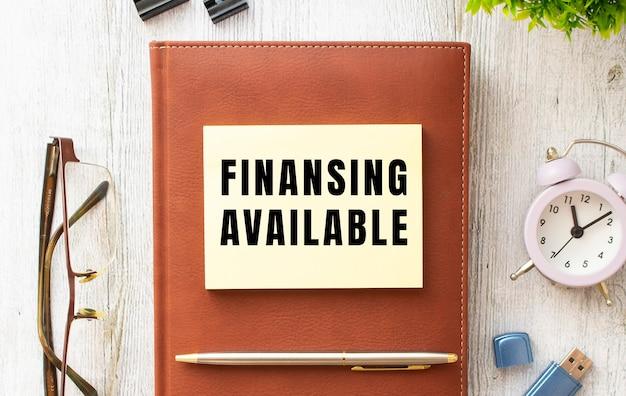 나무 테이블에 finansing available 텍스트가있는 메모장. 갈색 일기와 펜. 비즈니스 개념.