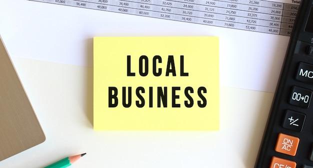 デスクトップ、ラップトップ、電卓、事務用品の近くに「localbusiness」というテキストが書かれたメモ帳。ビジネスコンセプト。