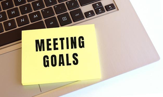 Meeting goalsというテキストが書かれたメモ帳は、ラップトップのキーボードにあります。ビジネスコンセプト。