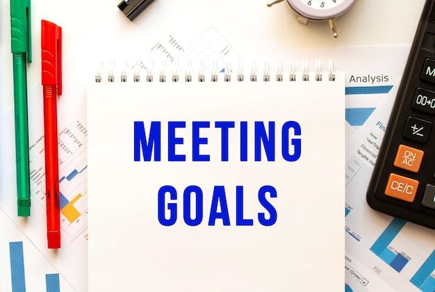 Блокнот с текстом встречи целей на цветной финансовой диаграмме. ручка, калькулятор на офисном столе.