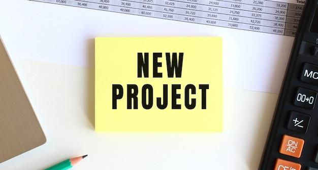 デスクトップ、ラップトップ、電卓、事務用品の近くに「newproject」というテキストが書かれたメモ帳