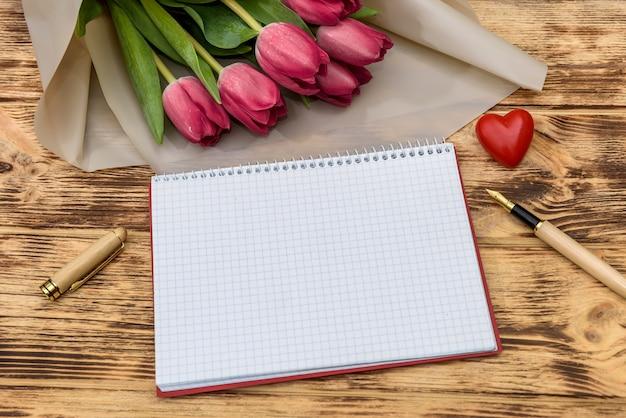Блокнот с букетом тюльпанов на деревянном фоне вид сверху