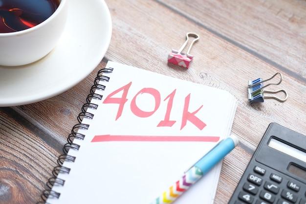 흰색 책상에 401k 단어로 메모장을 닫습니다.