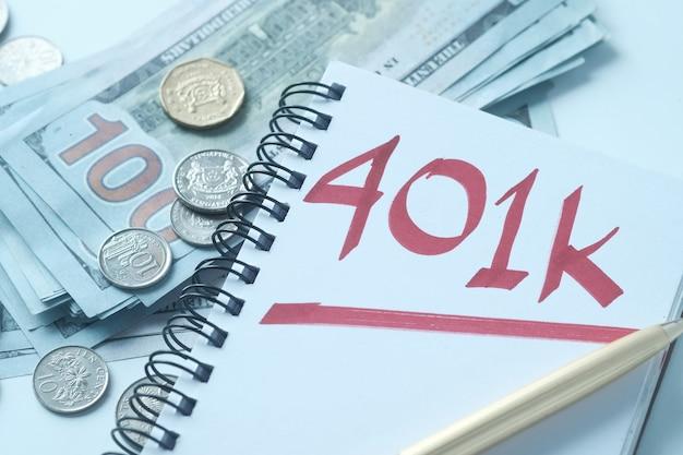 흰색 테이블에 단어 401k와 메모장을 닫습니다,