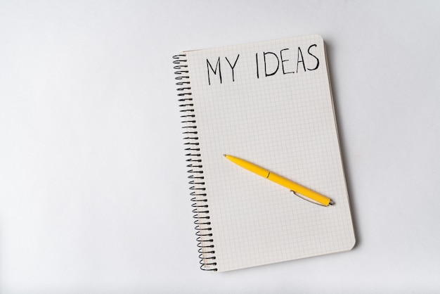 Notepad with words my ideas on white background. top view, pen on notebook