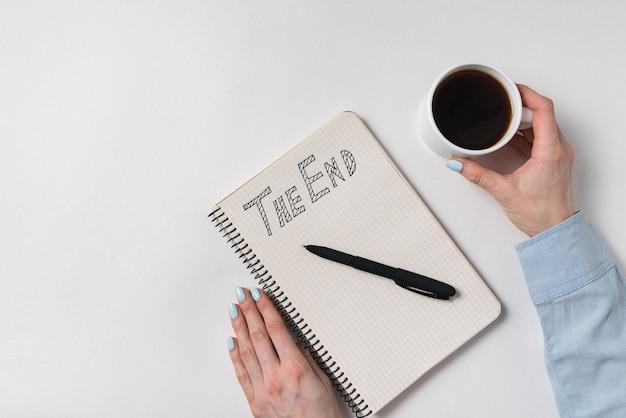 Блокнот со словами конец. женские руки с чашкой кофе и тетрадью на белом.