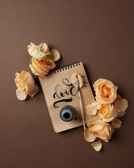 Notepad with written word love and flowers on a brown table, flat lay