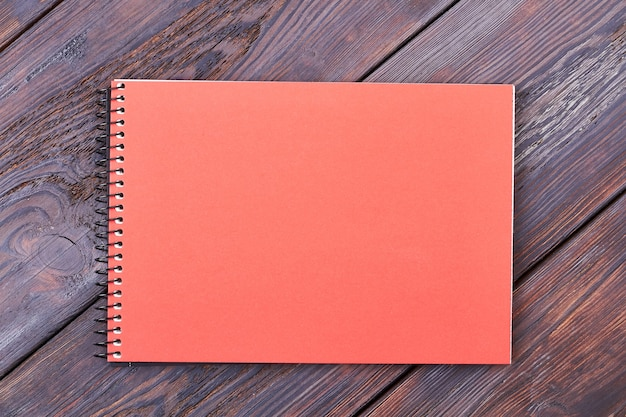 Notepad on wooden background. peach colored notebook. everyday life paper helper.