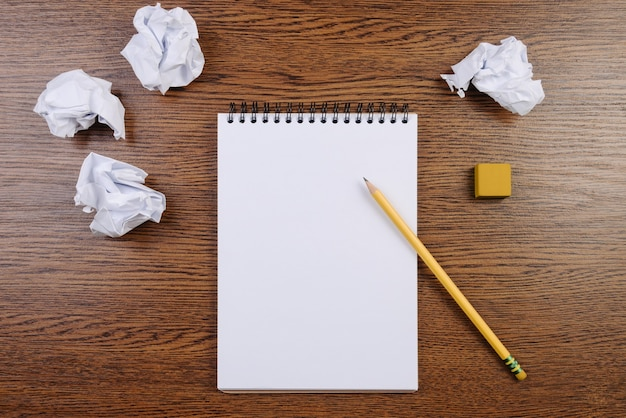 Notepad on a wooden table and crumpled sheets around.
