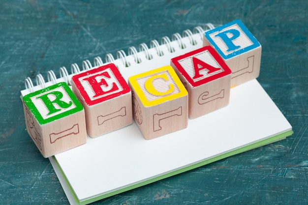 Notepad on wooden table and wood alphabet blocks