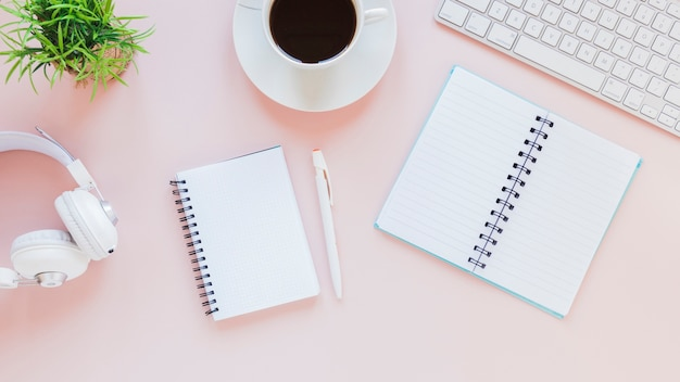 Блокноты и чашка кофе рядом с наушниками и клавиатурой