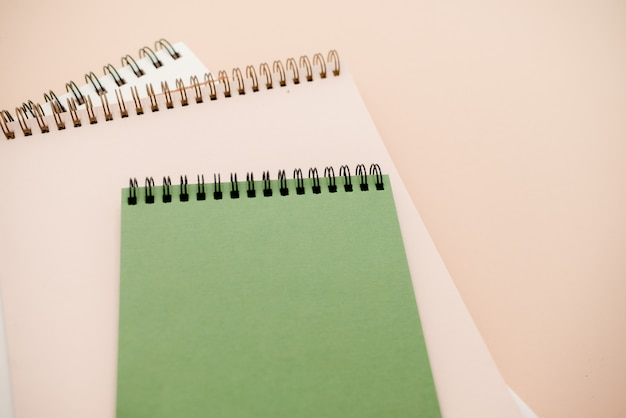 Notepads on beige background with copy space.