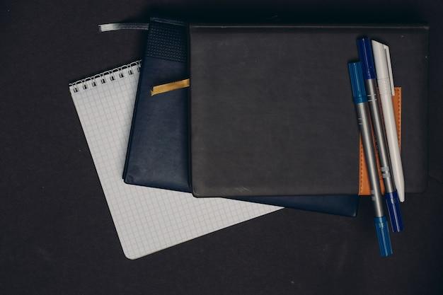 Блокноты документы книги ручки рабочий стол серый фон