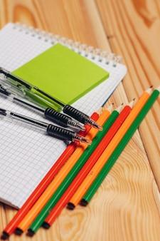 メモ帳鉛筆文房具学校アイテムワークデスク上面図。高品質の写真