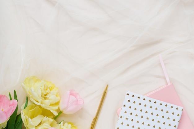 Блокноты с ручкой и розовыми желтыми тюльпанами на бежевом фоне стола