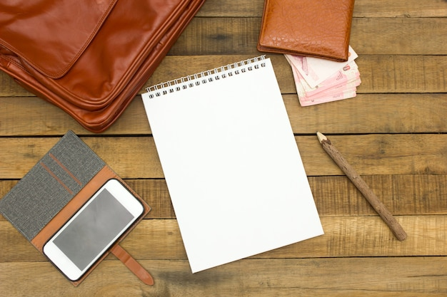 Notepaper, pencil, leather bag, wallet, money, mobile phone and equipment