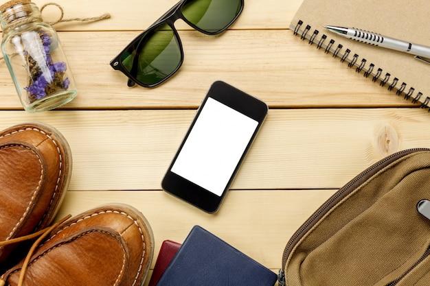 トップビューのアクセサリーは、パスポート、花、靴、携帯電話、サングラス、バッグ、時計、コピースペースのテーブル木製のnotepaperで旅行します。