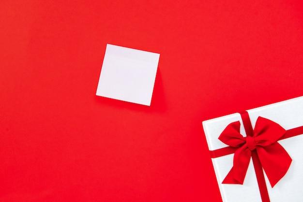 ギフトボックスと赤の背景に空のnotepaper