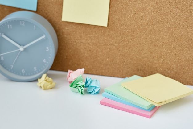 Of notes, goals, memo or action plan. sticky notes on a cork board and alarm clock  in workplace office or home