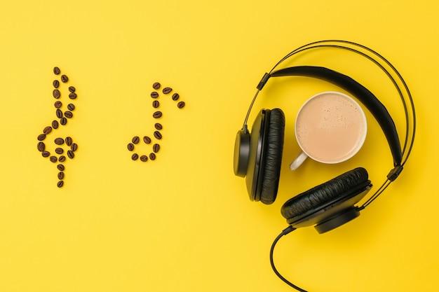 원두 커피, 헤드폰 및 노란색 배경에 커피 한 잔의 노트. 음악 쓰기의 개념. 음악 트랙 녹음 용 장비. 상단에서보기. 평평하다.