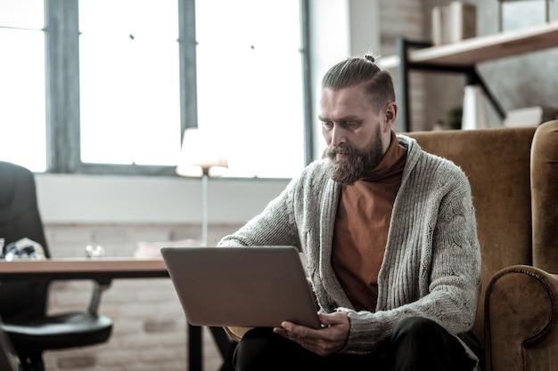 Заметки на ноутбуке. профессиональный бородатый консультант делает заметки на своем ноутбуке, слушая клиента