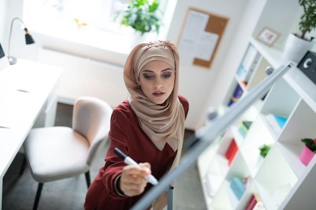 ホワイトボードに関する注意事項。ホワイトボードにメモを作る素敵な化粧をした若いイスラム教徒の教師の上面図