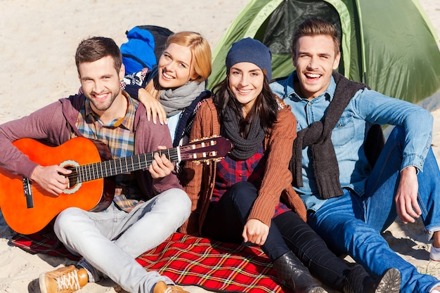Nothing but the best friends. top view of four young happy people sitting near the tent together while young handsome man playing guitar and smiling