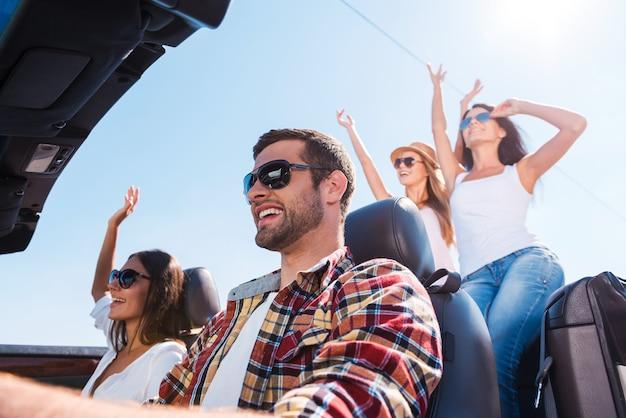 Ничего, кроме хороших друзей и путешествия. низкий угол обзора молодых счастливых людей, наслаждающихся поездкой в кабриолете и поднимающих руки