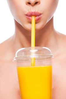 フレッシュオレンジジュース以外は何もありません!白い背景に立っている間ジュースを飲む美しい若い上半身裸の女性のクローズアップ
