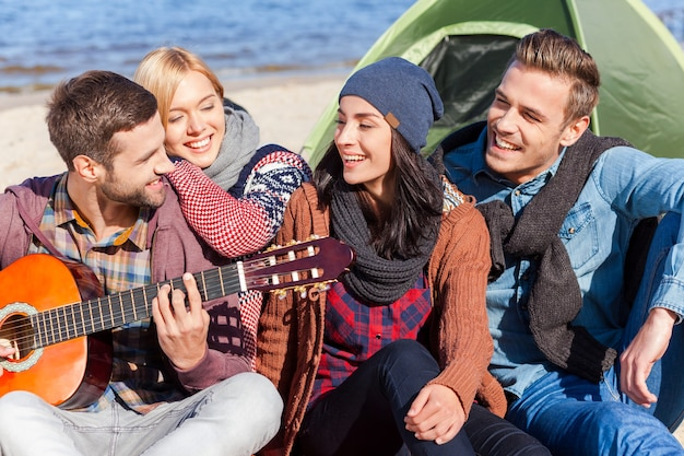 Nothing but friends and guitar. group of young cheerful people sitting at the riverbank together while young handsome man playing guitar and smiling