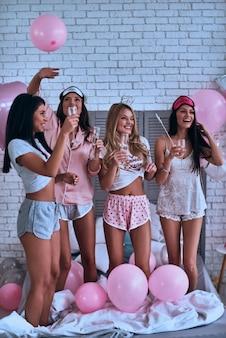 友達ほど良いものはありません。眠りのパーティーをしながらシャンパンを飲むパジャマ姿の4人の魅力的な若い笑顔の女性の全長