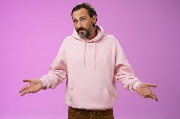 Nothing man could do. mature bearded guy grey hair 40s spread hands dismay cannot help gesture frowning apologizing shrugging unaware standing perplexed not know anything, purple background.