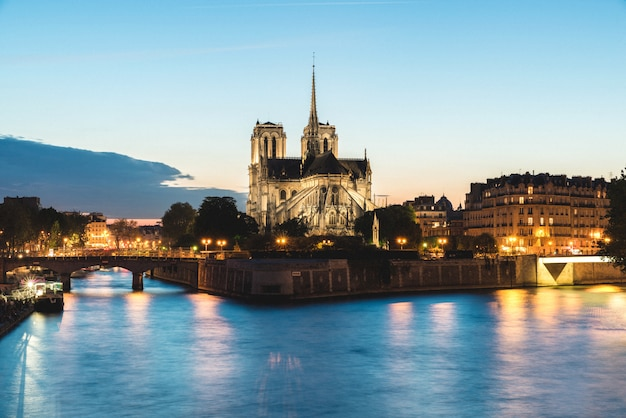 Notre dame de paris cathedral with seine river at night in paris, france.